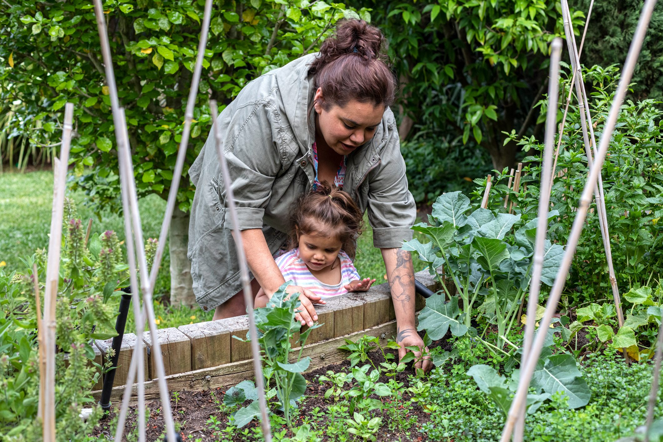 Indigenous women helping her young daughter in the garden