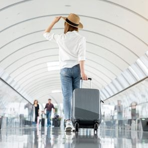 Young woman wearing casual clothes and walking in the airport hall