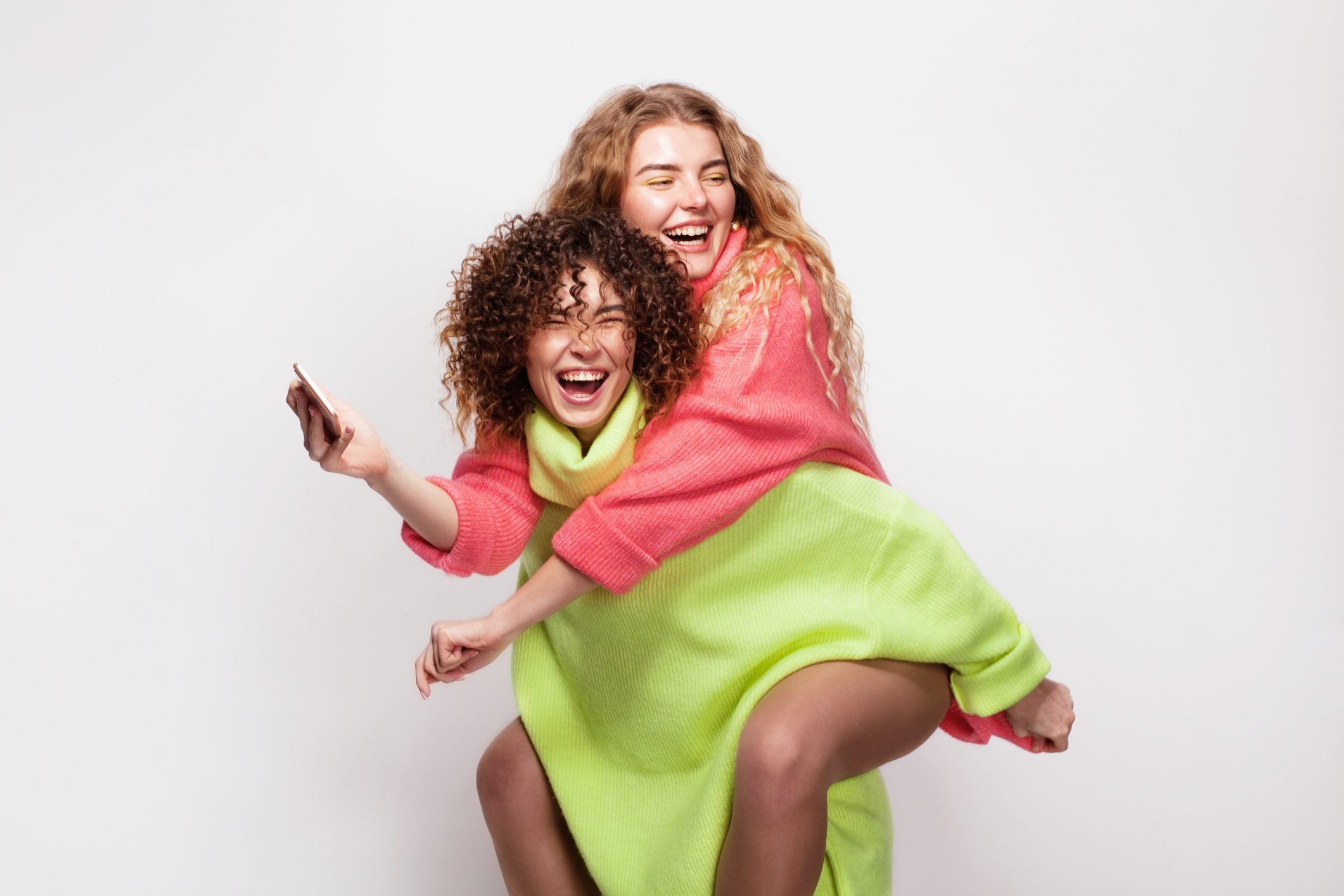 Two joyful beautiful women having fun together