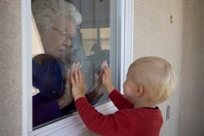 Mary-Lou McCullagh, 83, and her husband Bob, 84, greet Axel Stirton, 2, the little boy who lives across the street through the closed window