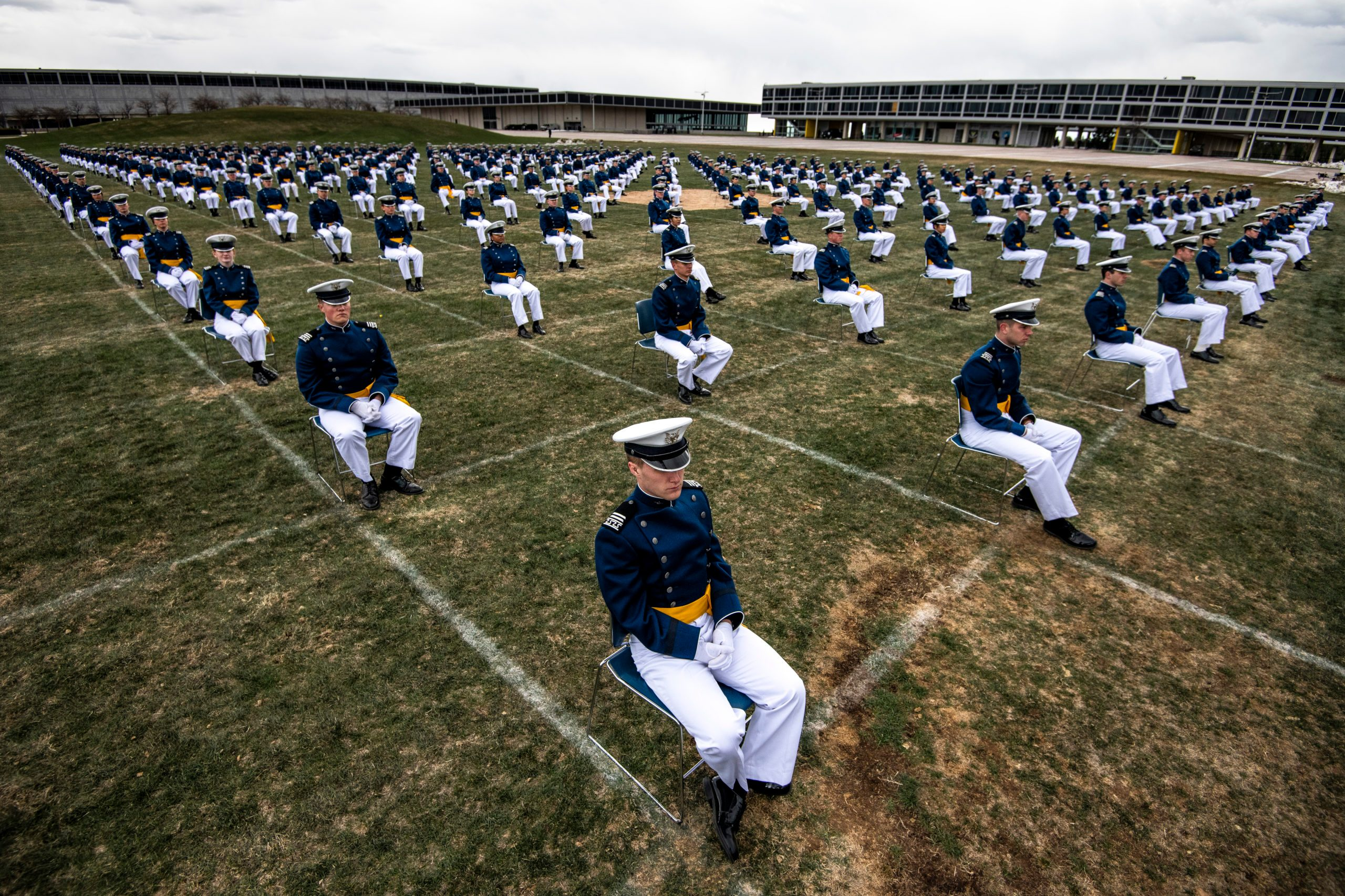 Air Force Academy cadets, spaced eight feet apart, listen to a commencement address