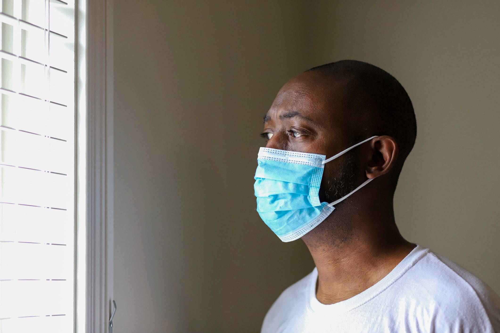 man with face mask in house looking out window