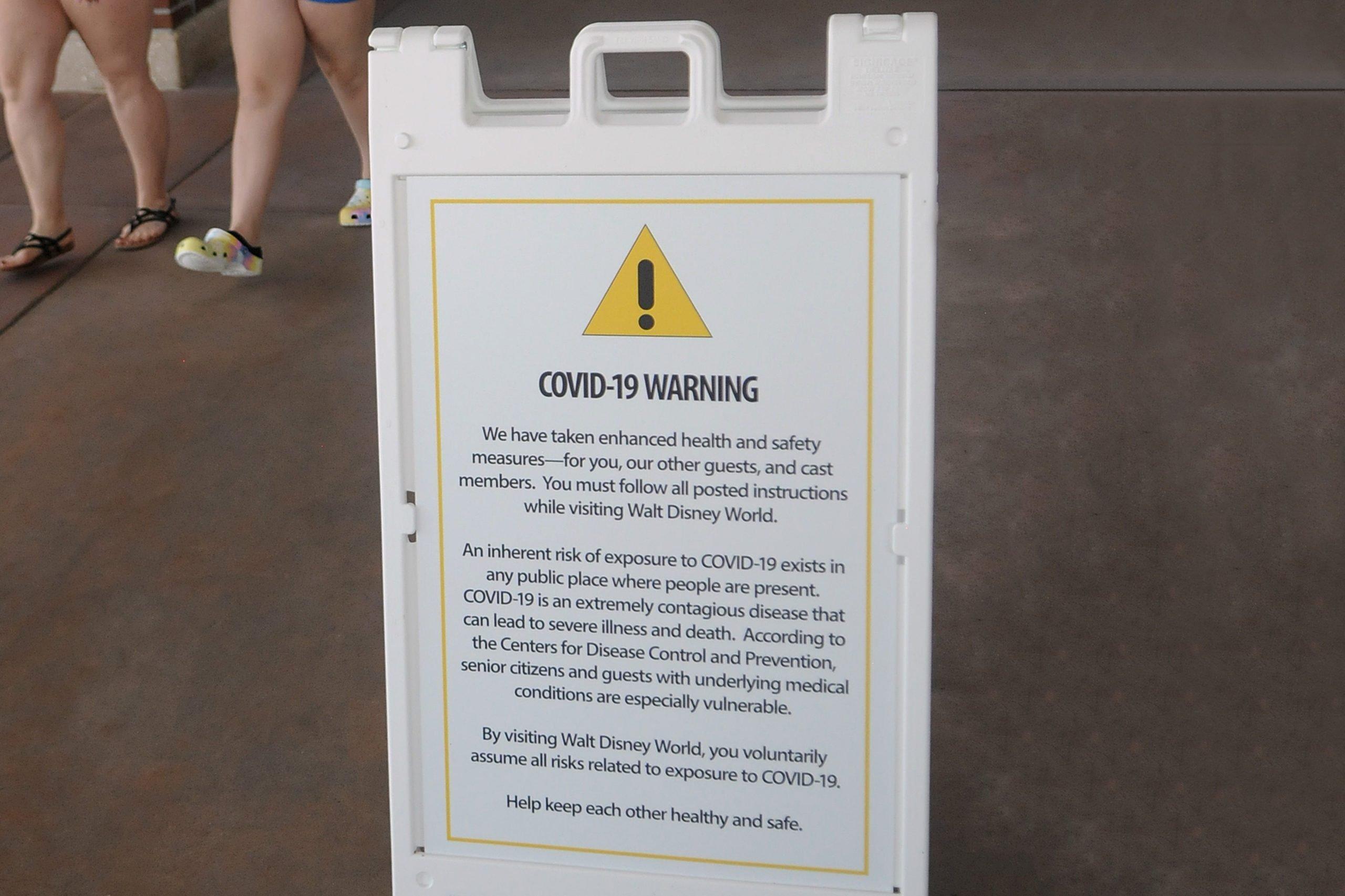 A COVID-19 warning sign is seen at Disney Springs at Walt