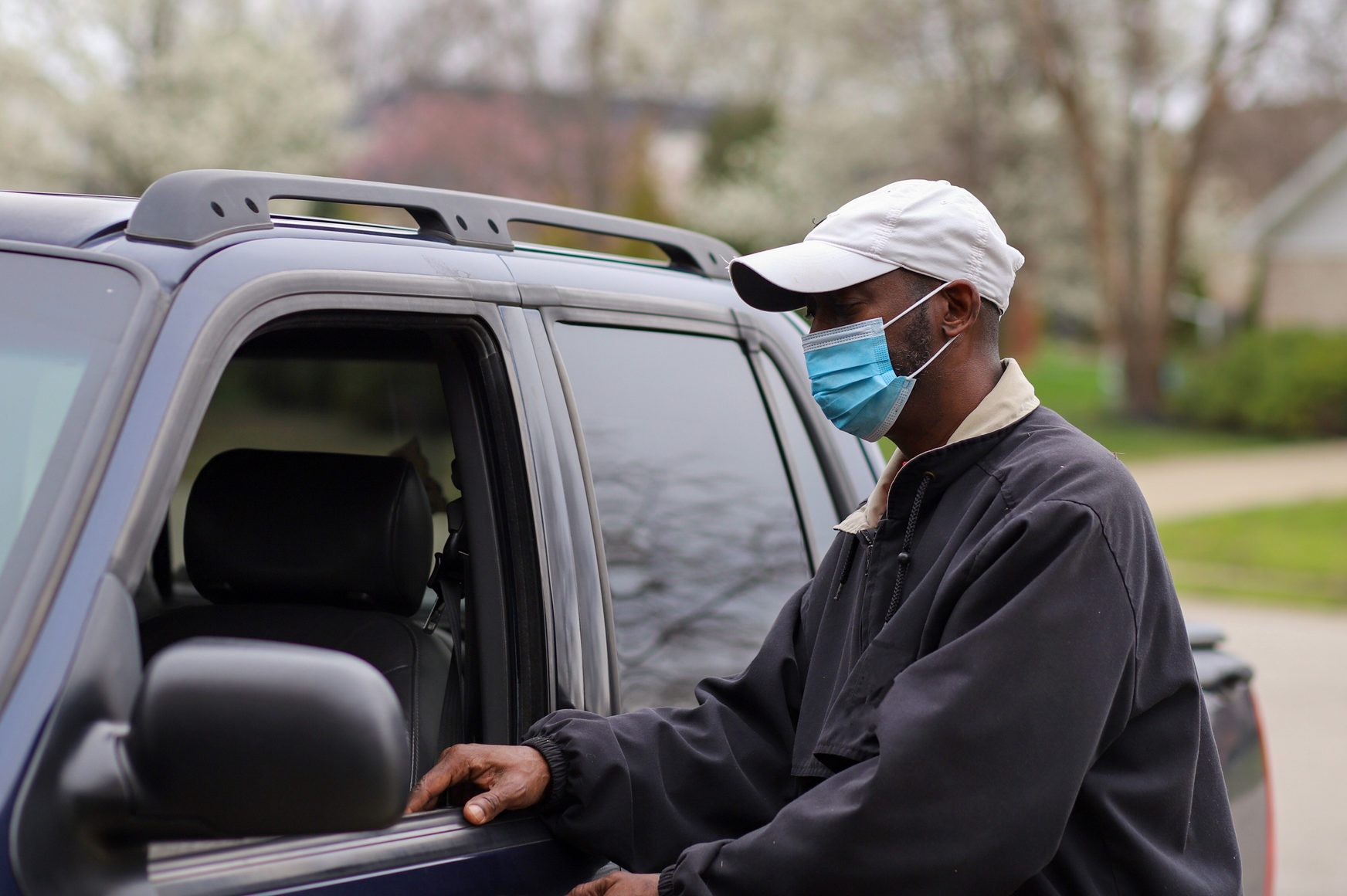 African-American man leaving in his truck wearing a mask to protect him from a virus infection