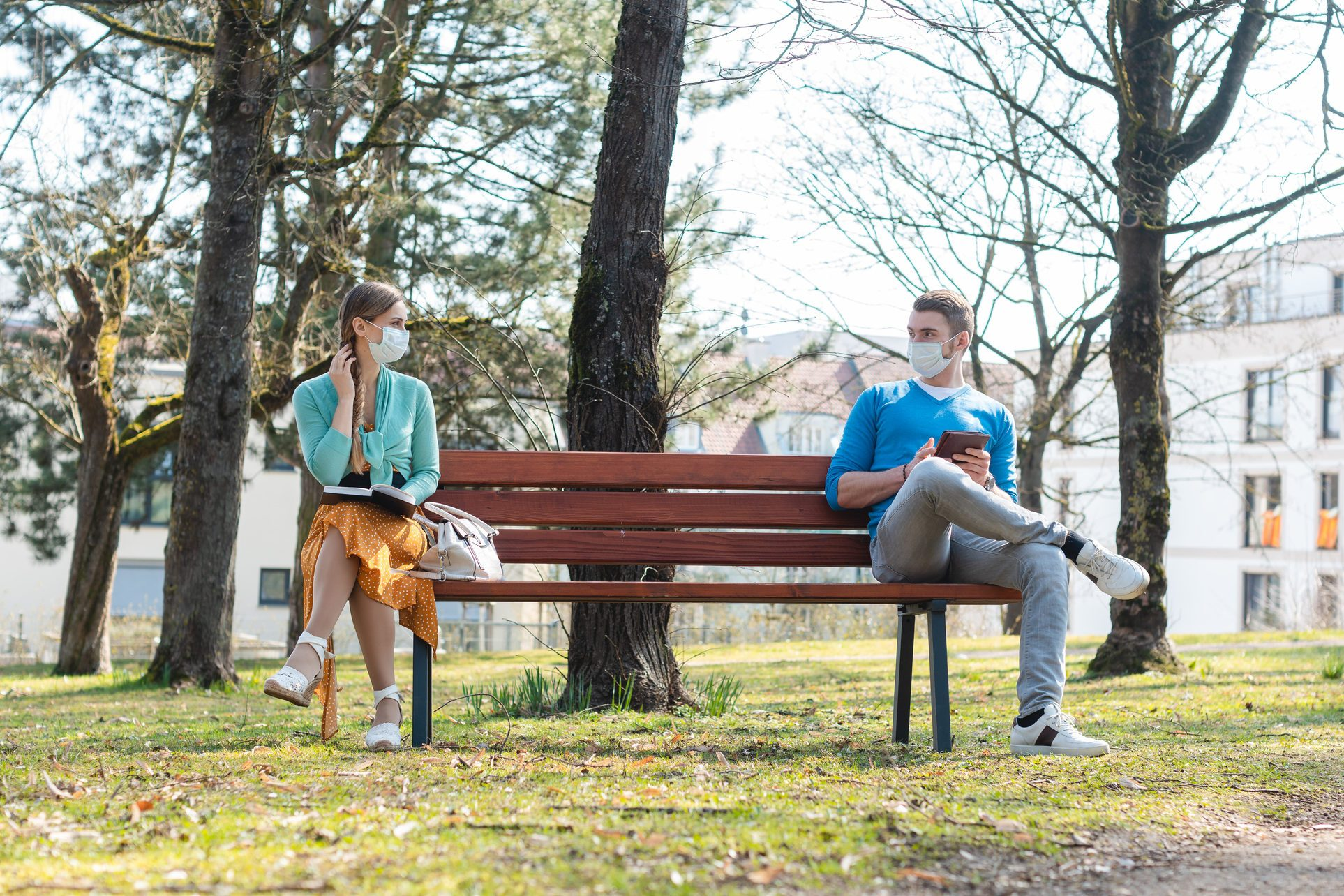 Woman and man with face mask in social distancing flirting