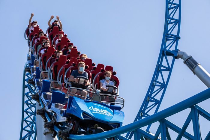 Masked people separated on a running roller coaster