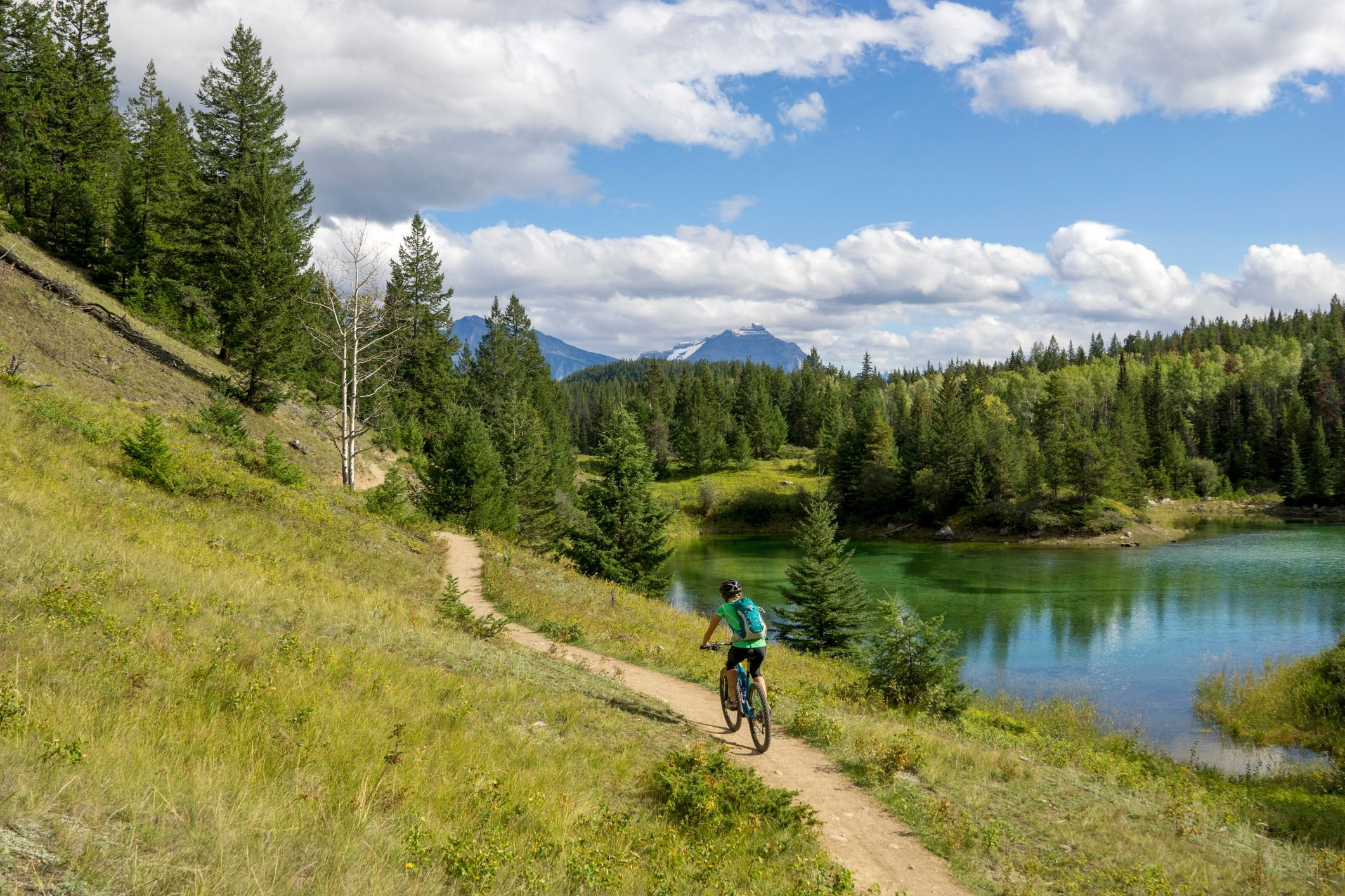 A woman mountain biking a scenic trail near a lake.