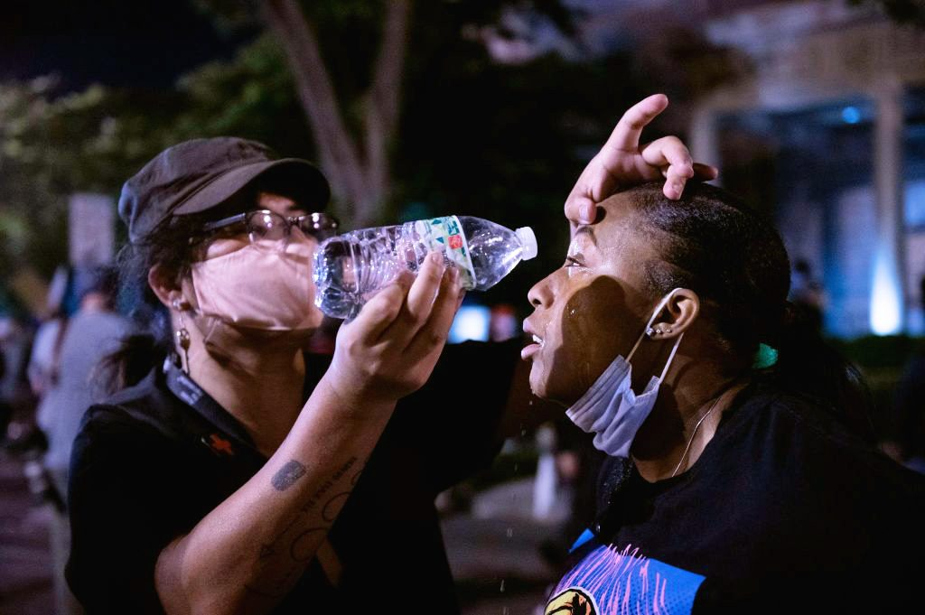 woman pouring water into another woman's eyes after being tear gassed during protest