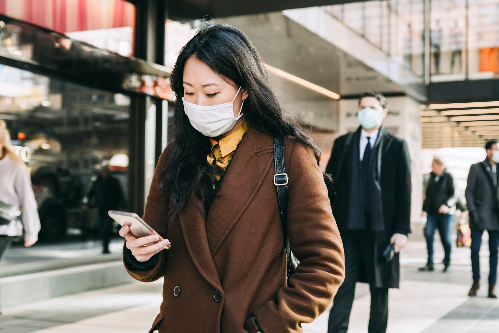 Woman with face mask walking in street using smartphone