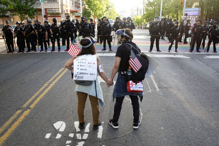 rear view shot of two protestors holding hands, american flags, and first aid kits