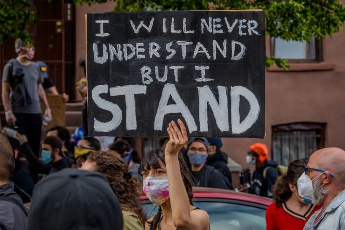 A participant holding a sign at the protest. Thousands of...