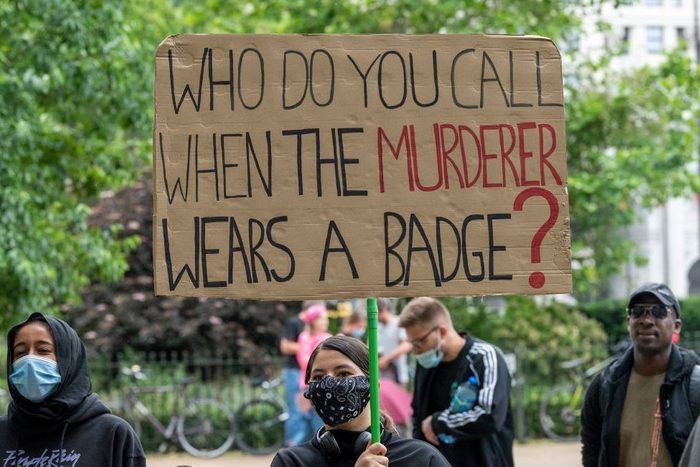 A protester holds a placard with Who do you call when the...