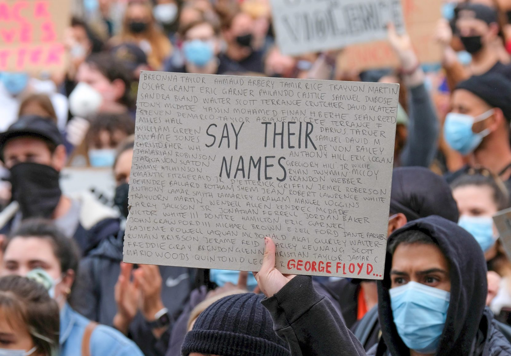A protester wearing a face mask holds a placard saying say...
