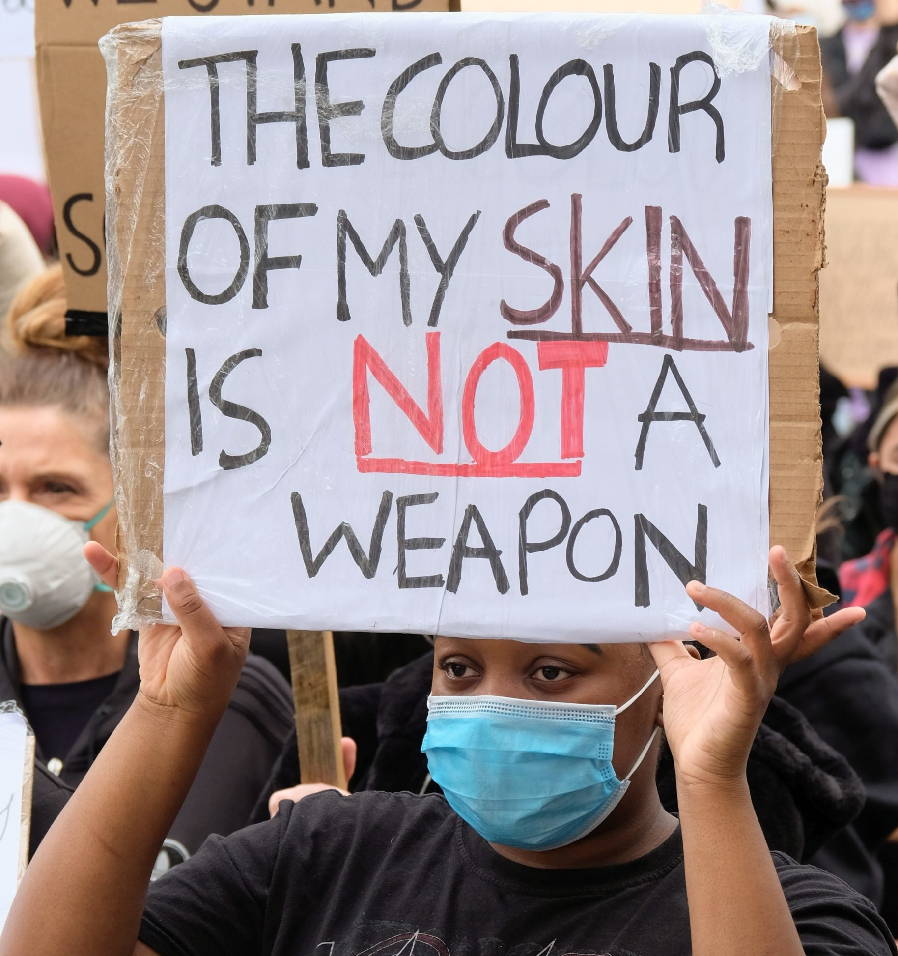 A protester wearing a face mask holds a placard saying the...