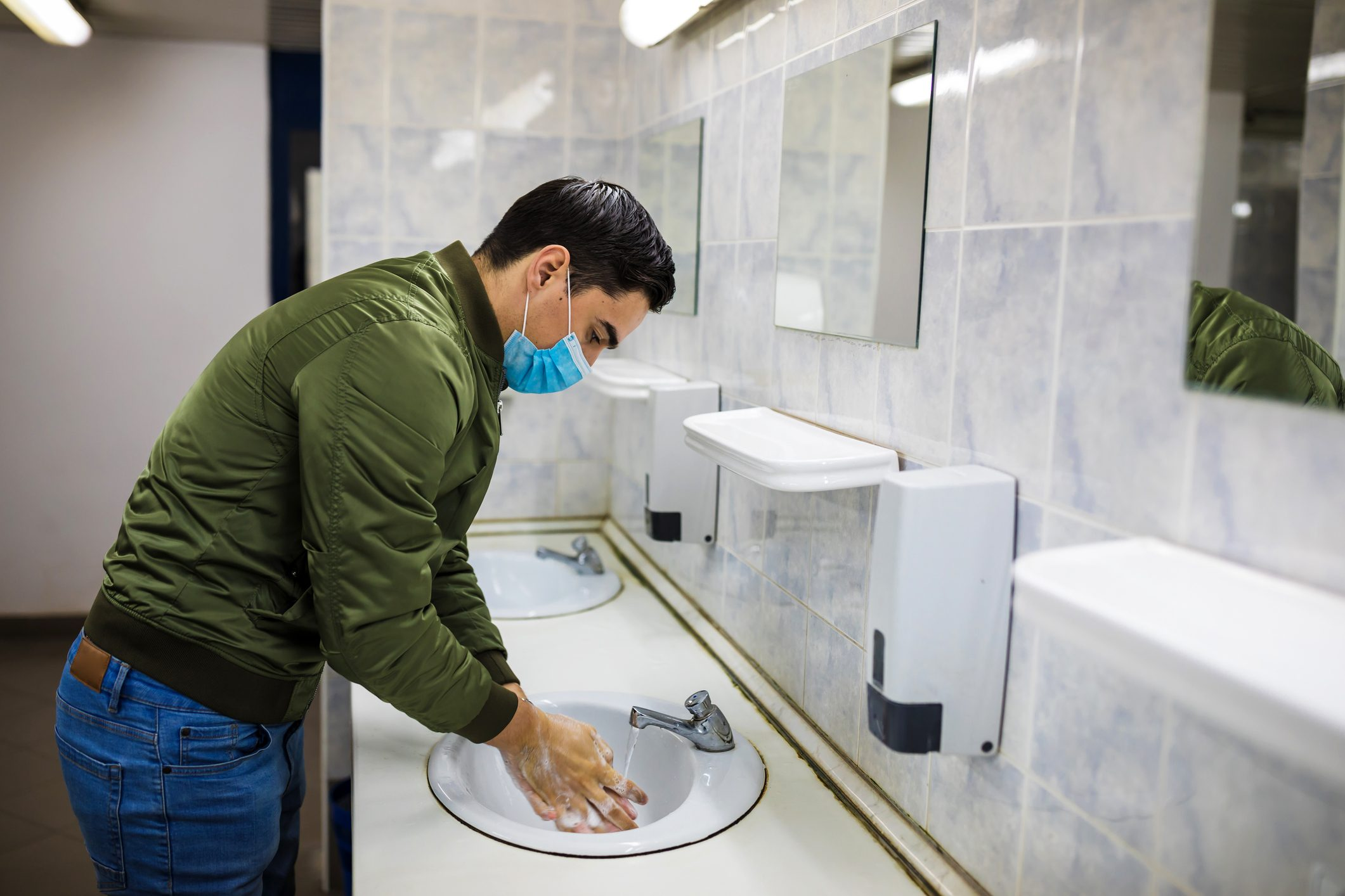 Man washing his hands to avoid diseases like coronavirus Man with a face mask washes his hands in a public bathroom