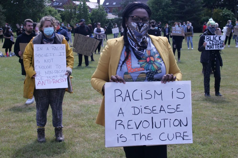 Protesters wearing face masks hold placards during the...