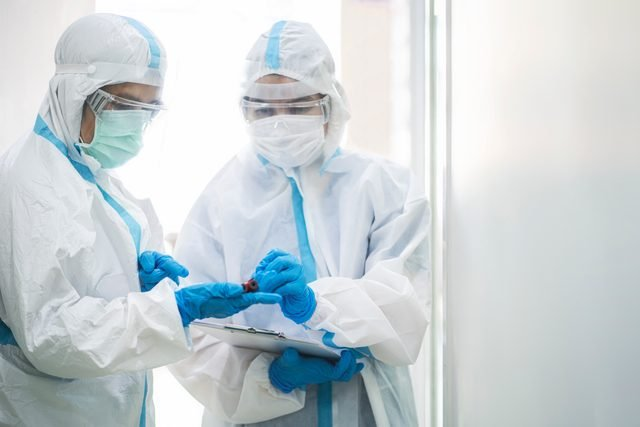 Asian doctor in PPE medical suit holding coronavirus or covid-19 blood testing tube in quarantine room