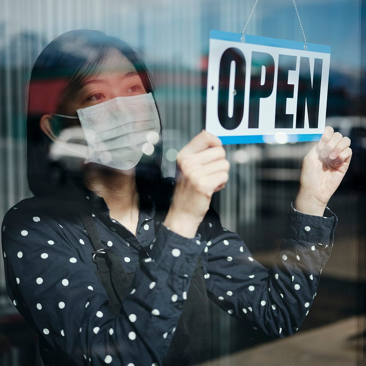"woman flipping sign to ""open"""