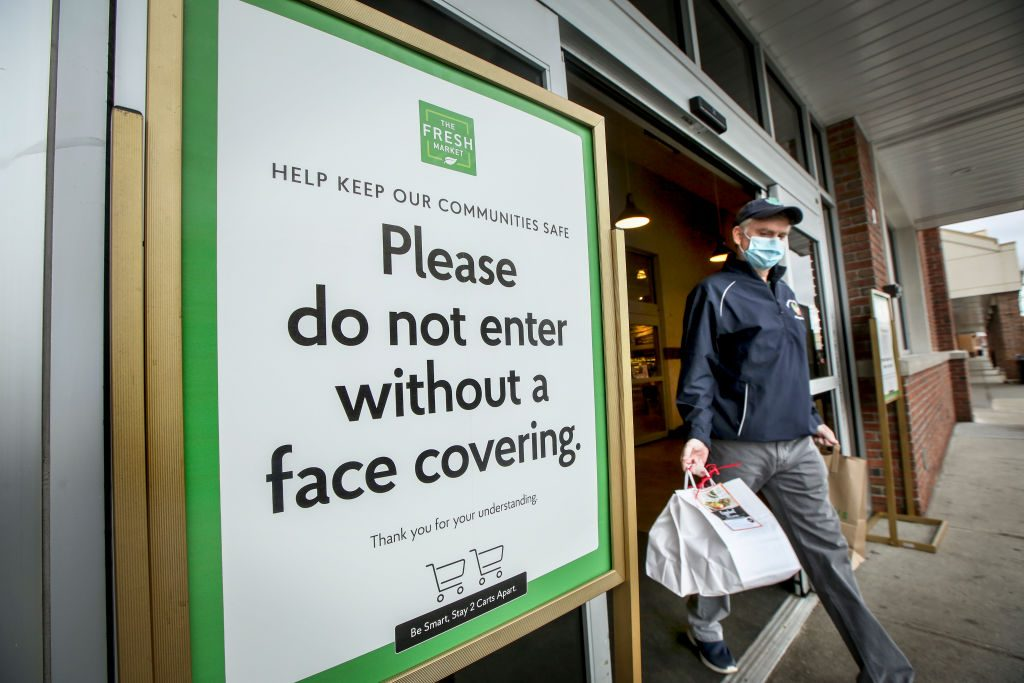 A Sign Outside of a Supermarket Asks Customers to Wear A Face Covering
