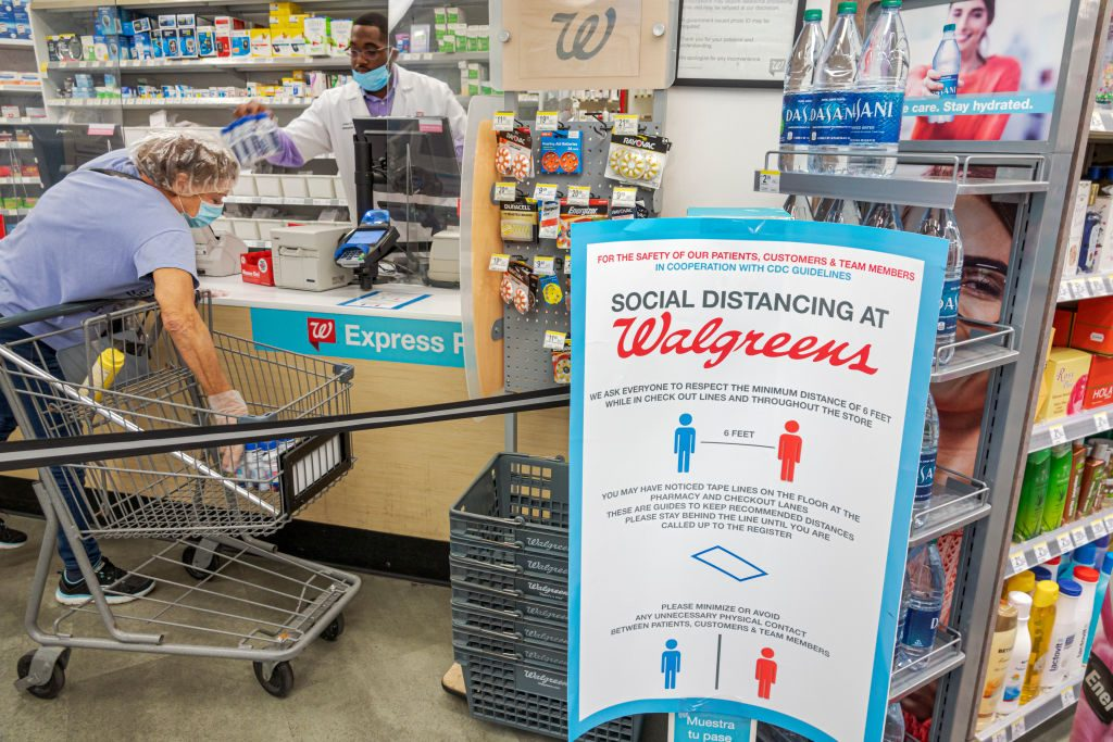 Florida, Miami Beach, Walgreens pharmacy, Social distancing at check out counter, with shopper and cashier both wearing PPE, face masks and gloves