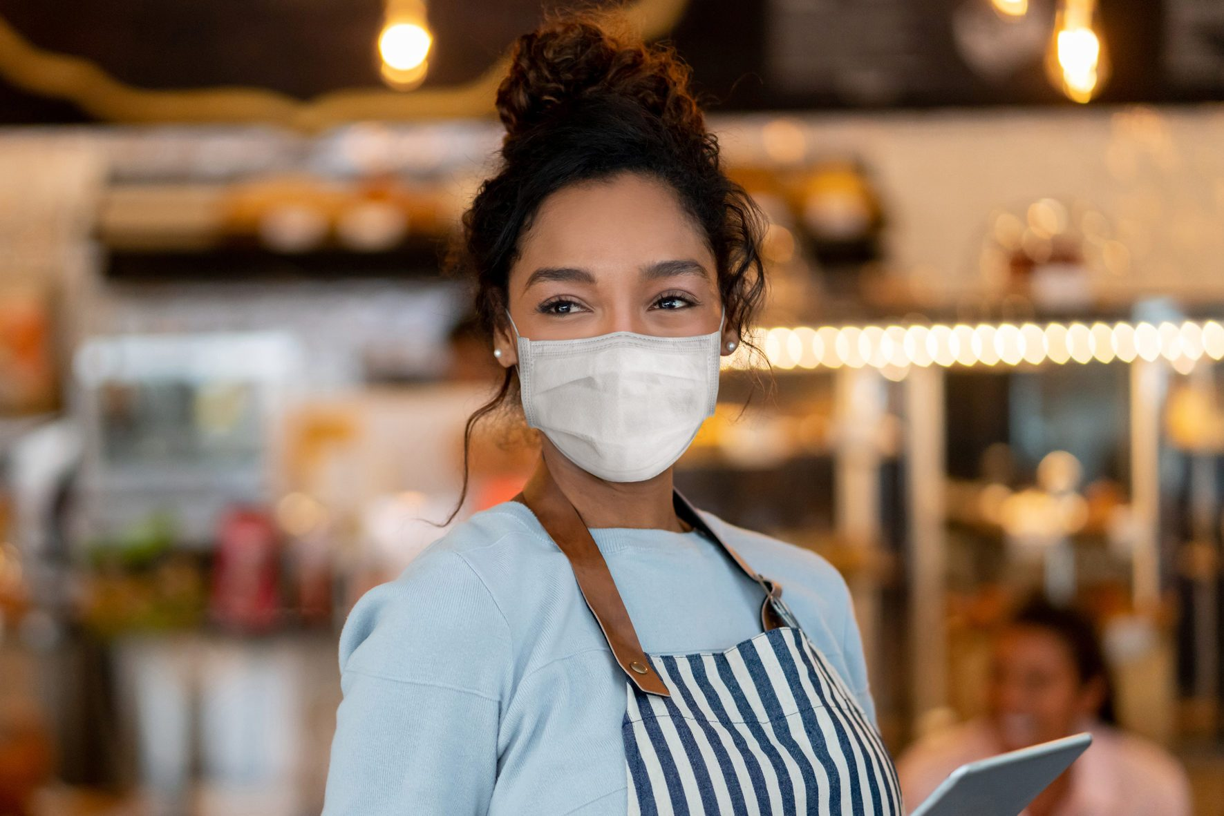 Beautiful waitress working at a restaurant wearing a facemask