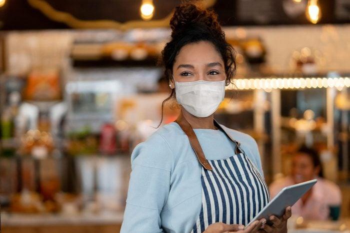 Beautiful waitress working at a restaurant wearing a facemask