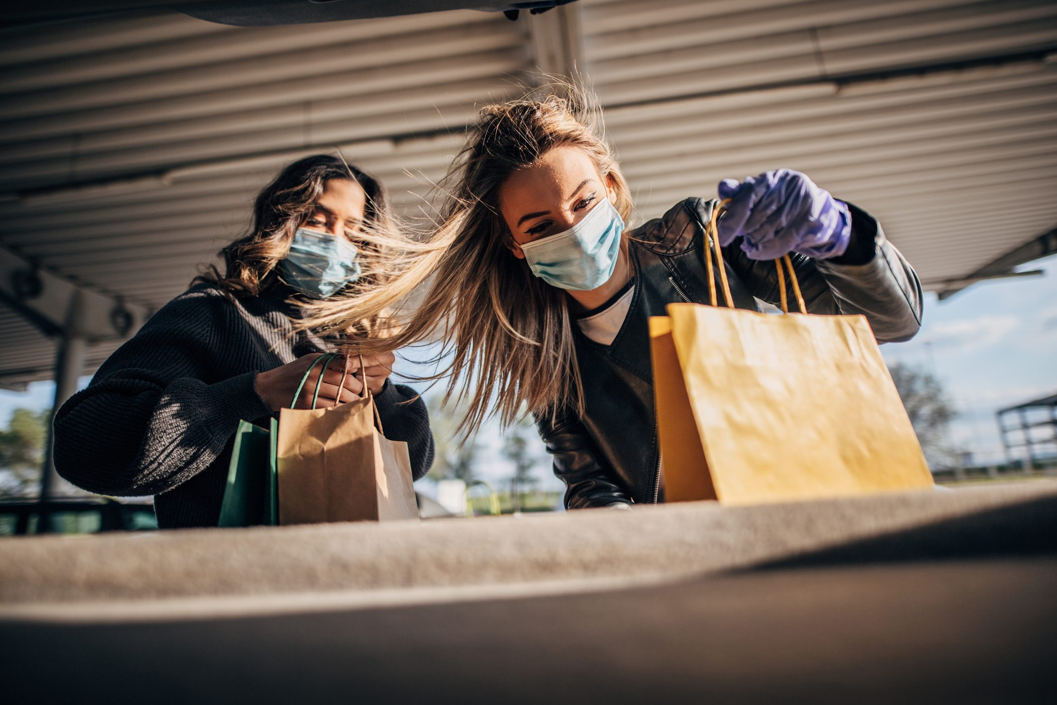 Women with protective masks and gloves finished shopping