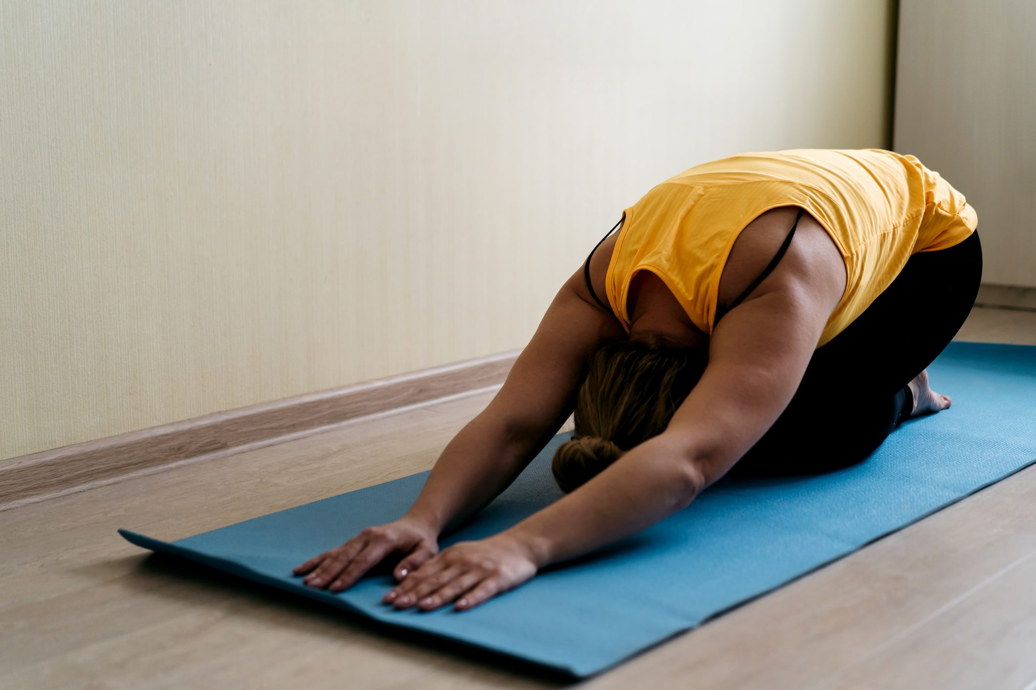 A middle-aged woman sitting in a yoga pose at home on a sports mat in casual sportswear meditating