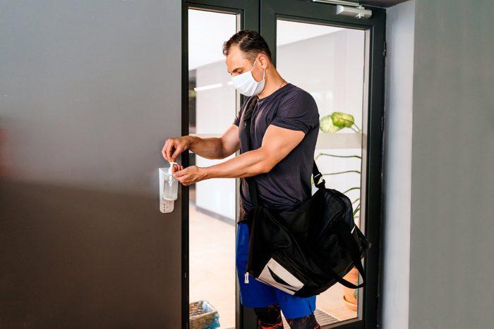 man using hand sanitizer at gym