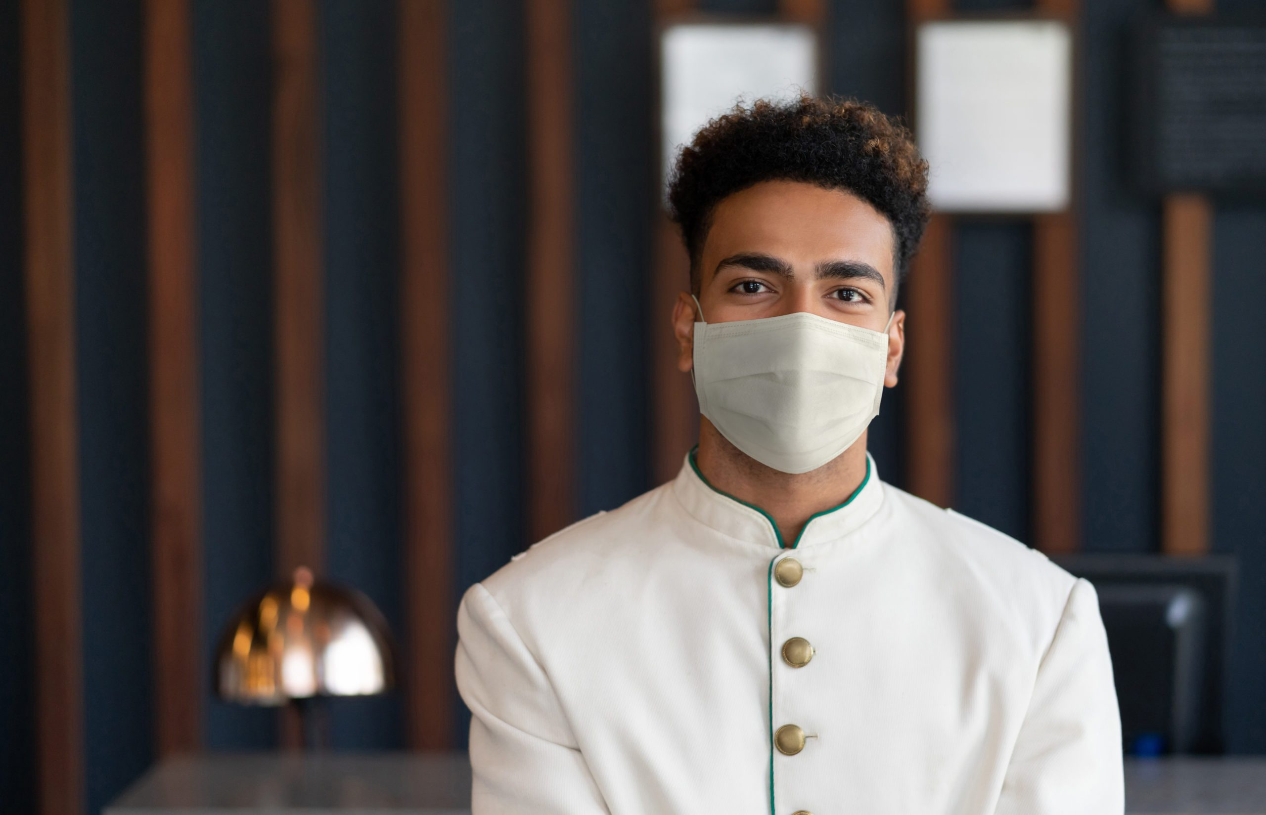 Happy bellhop working at a hotel and wearing a facemask to avoid COVID-19