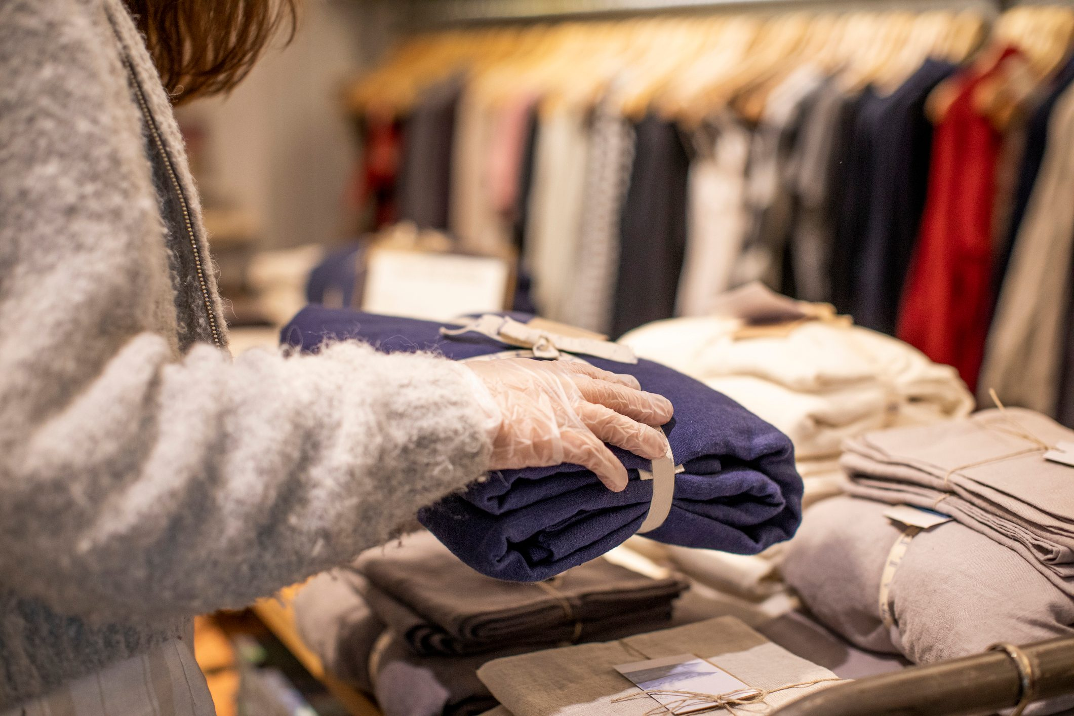 Close up on hands wearing protective gloves while working in fashion store.