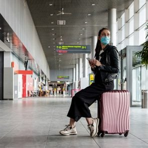 Young woman at the airport with luggage, wearing N95 face masks