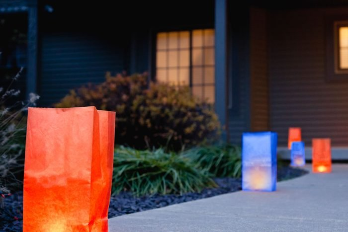 luminaria made from red and blue paper bags line the walkway of a house on the 4th of july