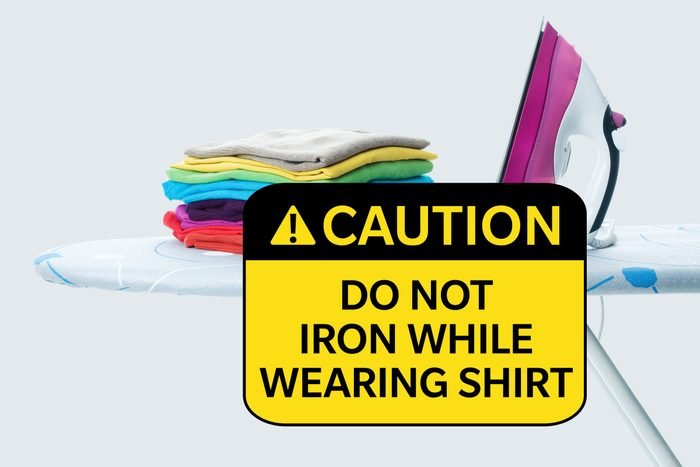 ironing board with shirts and iron. caution: do not iron while wearing shirt