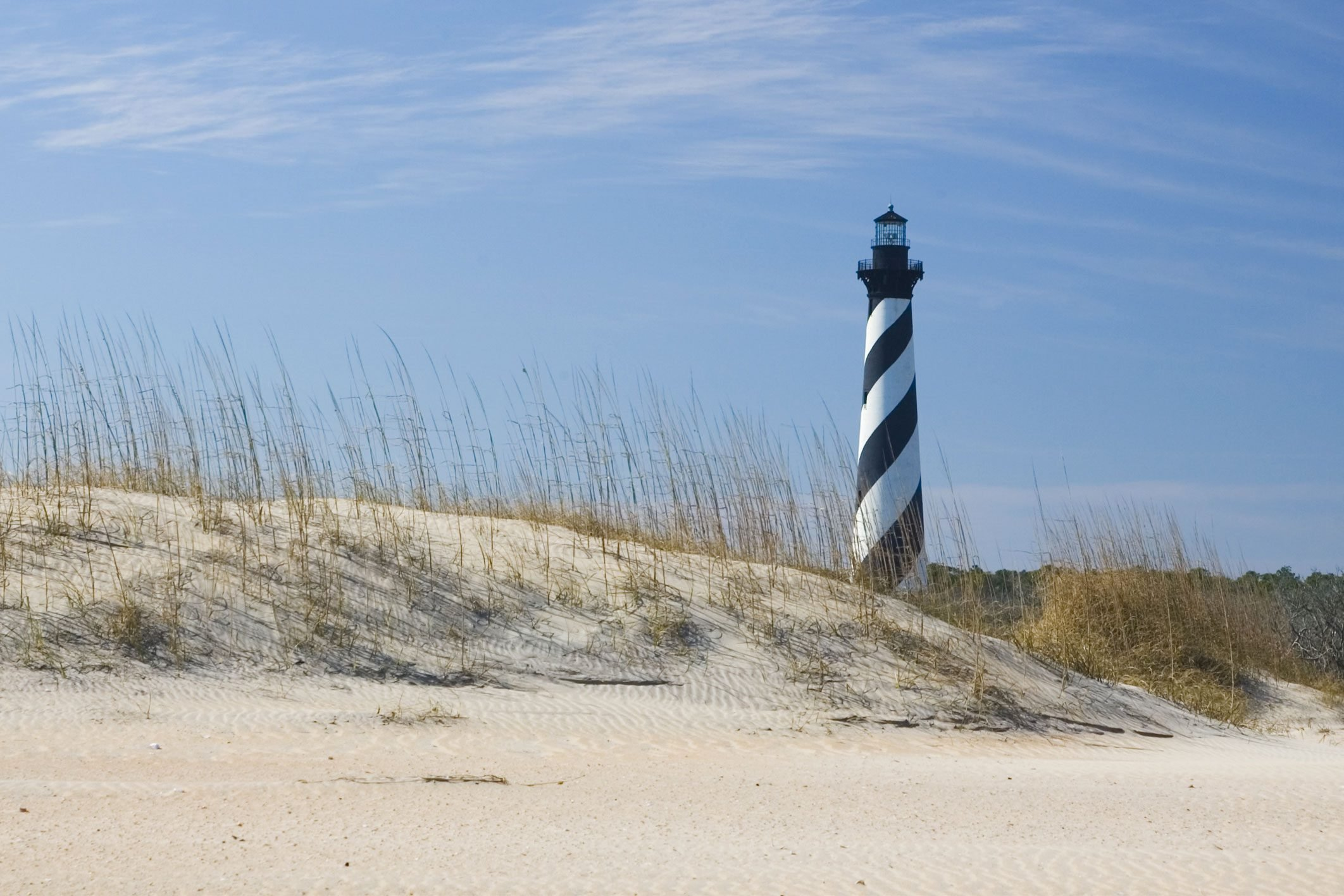 The Hatteras Lighthouse in North Carolina stands back on the beach behind the dunes.