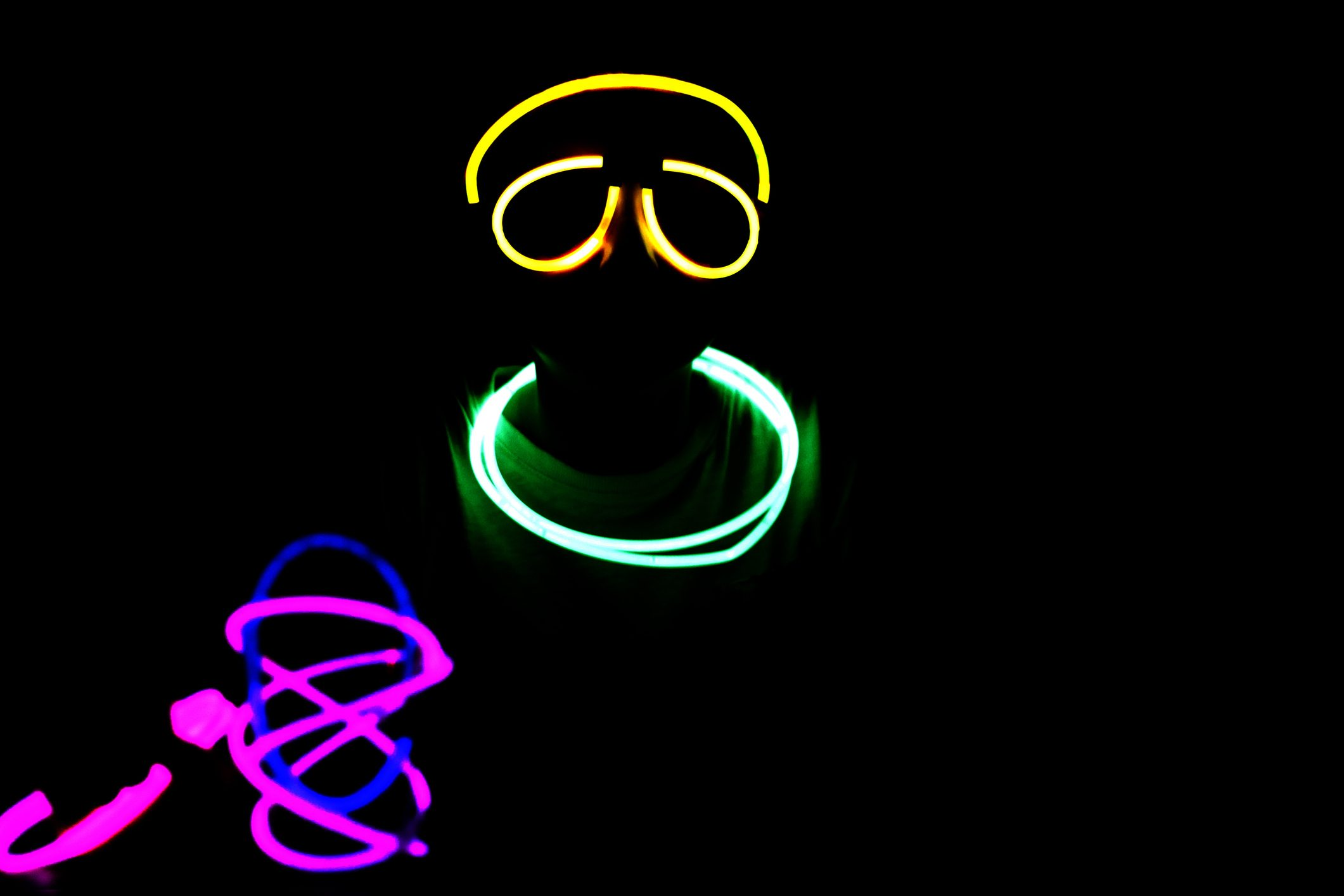 Person wearing colorful neon glow sticks at night