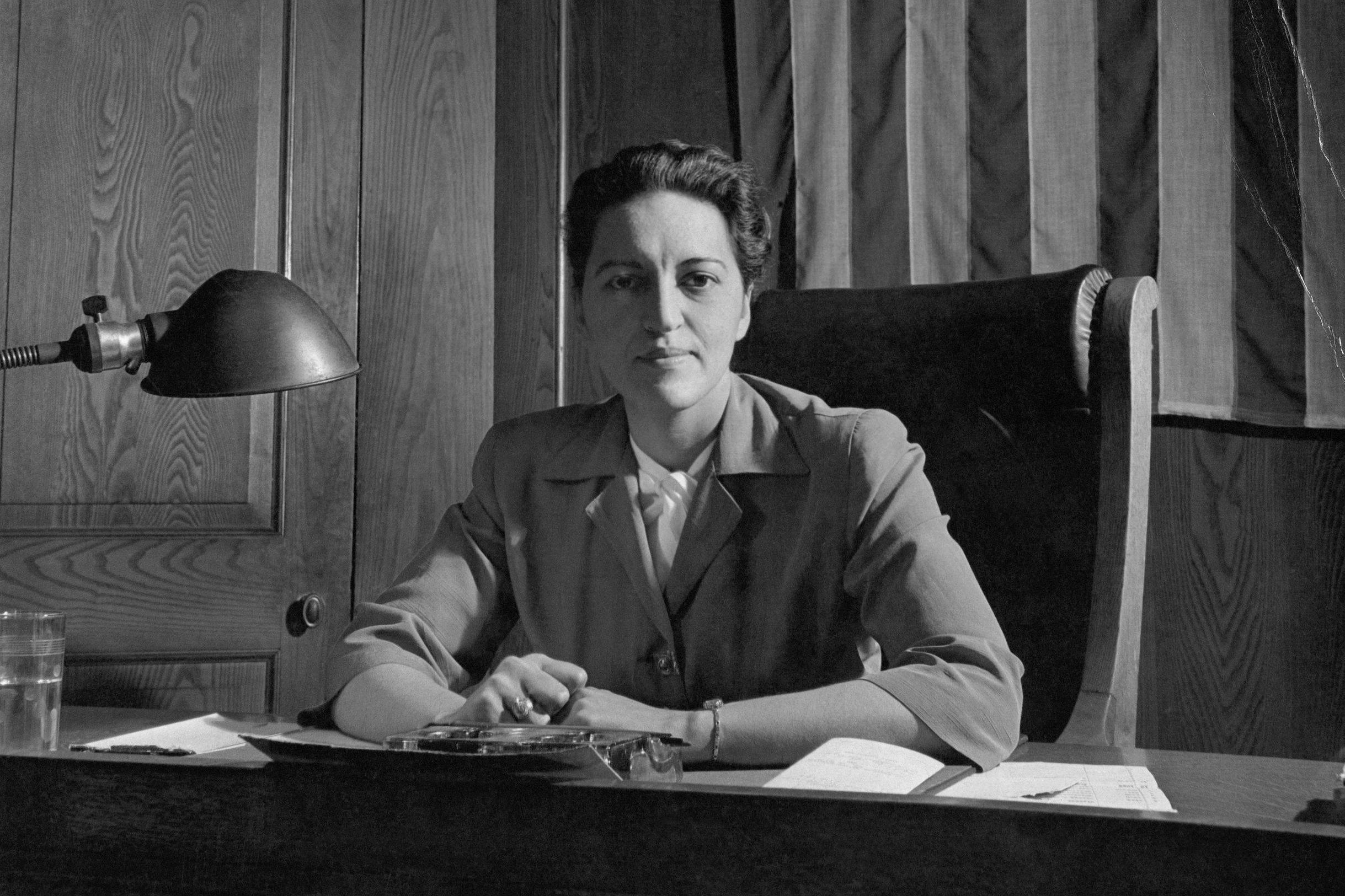 Justice Jane M. Bolin seated at her desk under an American flag