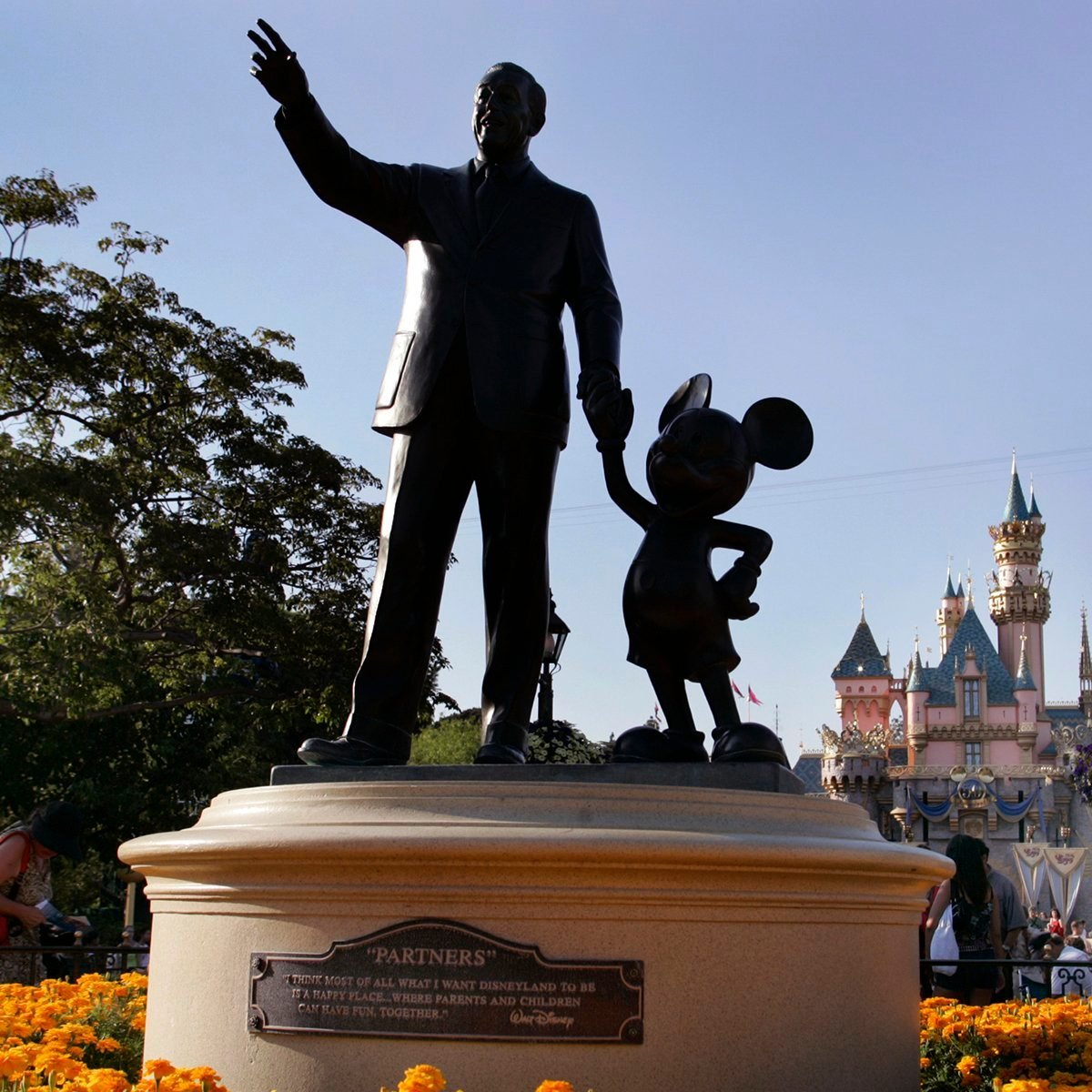 "Sleeping Beauty's Castle can be seen in the backround as people make their way past the ""Partners"" statue (depicting Walt Disney and Mickey Mouse) at Disneyland, Friday July 15, 2005, in Anaheim. Disneyland celebrated its 50th anniversary on July 17, 2005. (Photo by Richard Hartog/Los Angeles Times via Getty Images)"