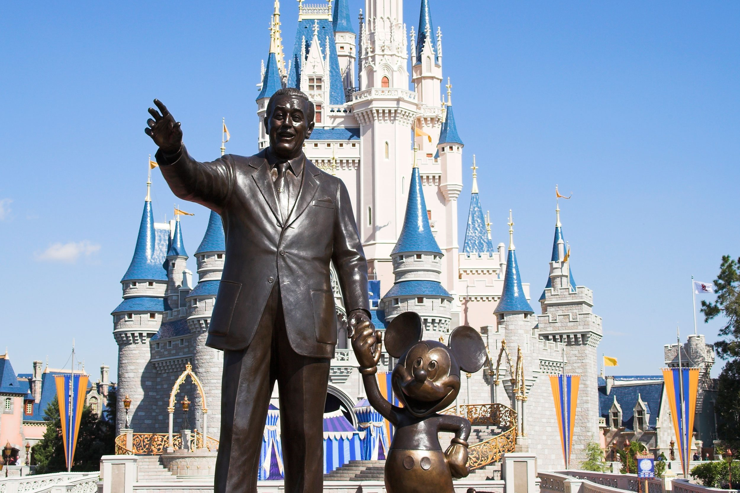 disney world. walt and mickey statue with cinderella's castle background.