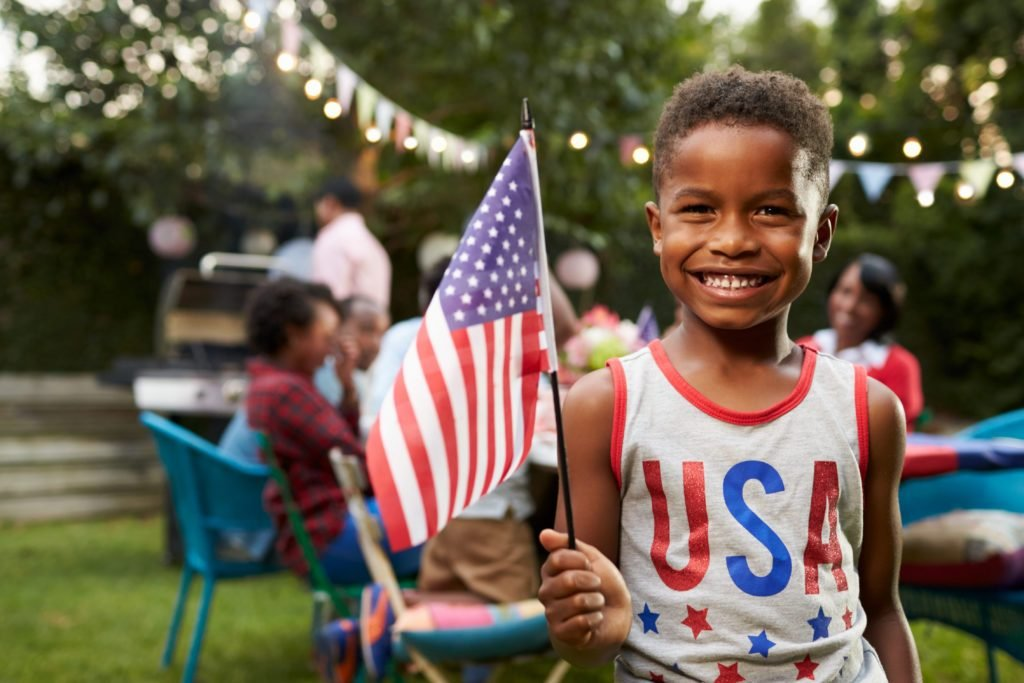 Young black boy holding flag at 4th July family garden