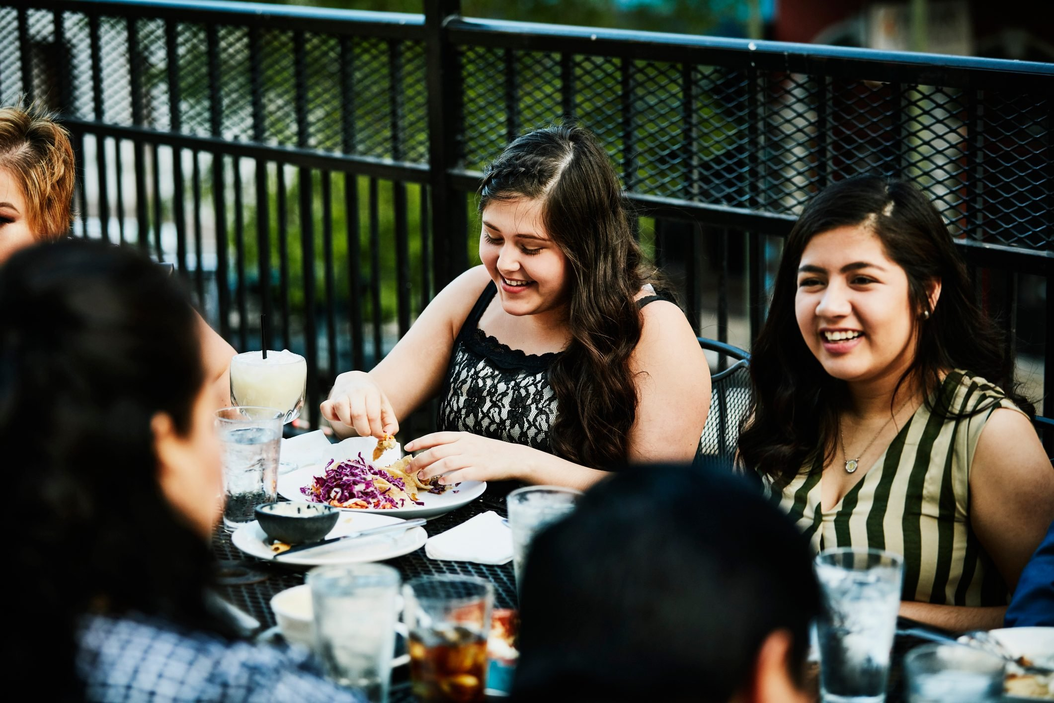 Laughing young women sharing a meal with family on restaurant deck