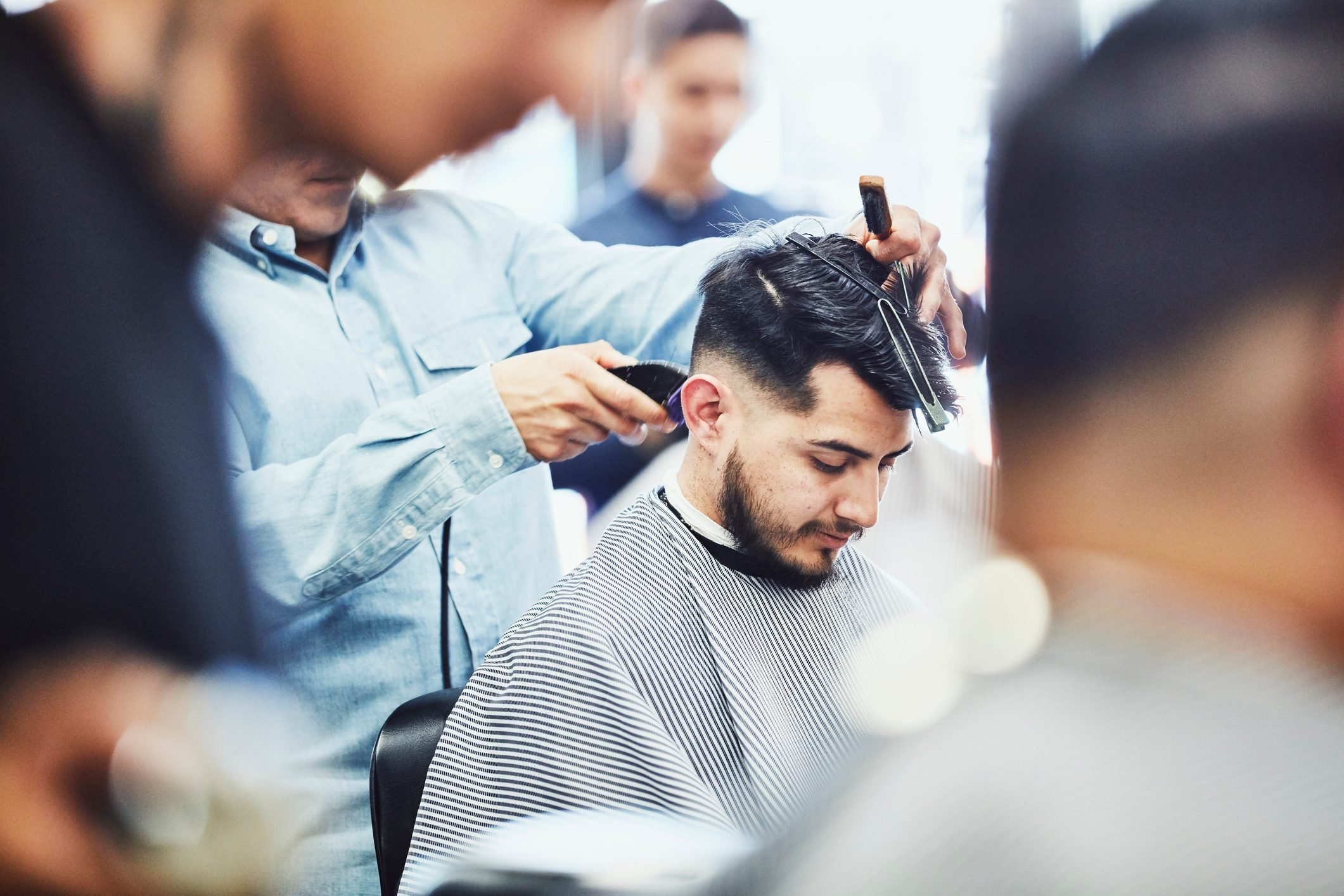 Man having hair cut in barber shop