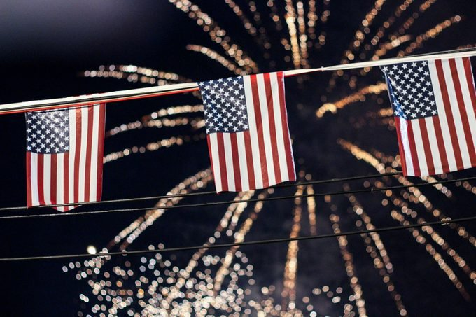 low angle of american flag fourth of july decorations with fireworks bursting in the background
