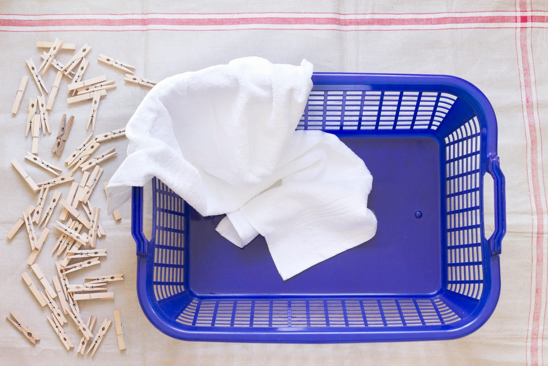 Clothes pegs, laundry basket and towel on cloth