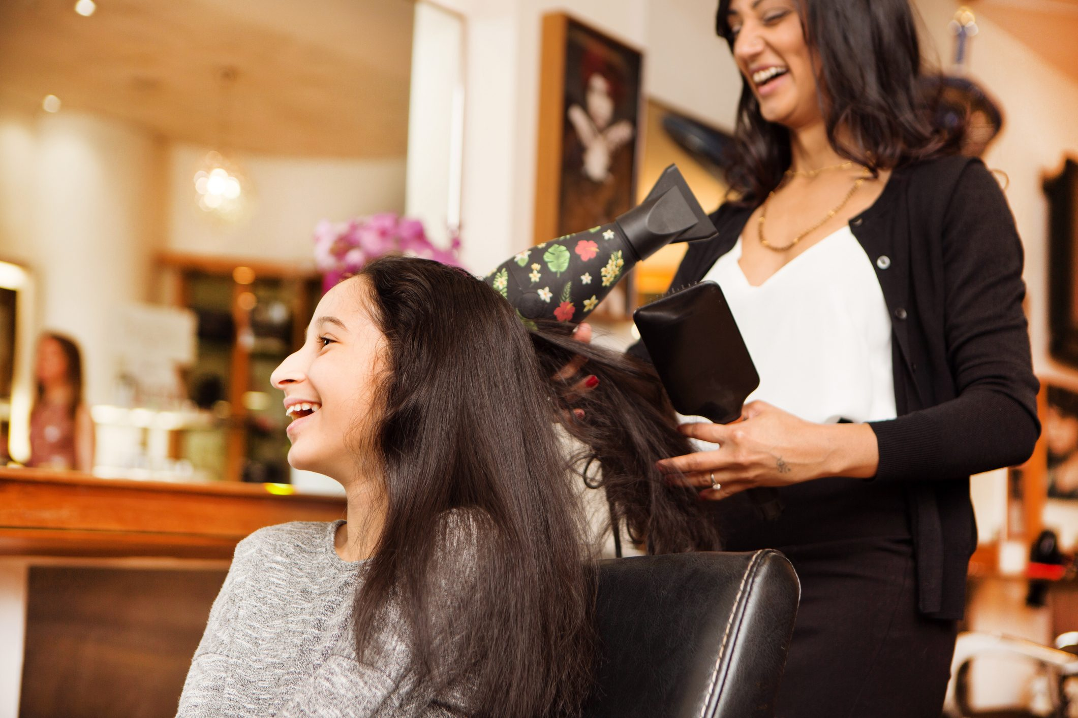 Hairdresser and girl laughing while having blow dry in hair salon