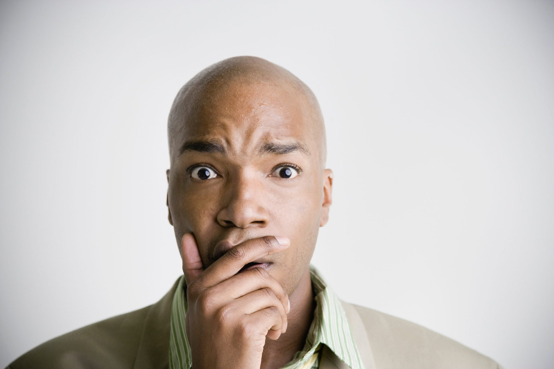 African businessman with hand covering mouth and chin