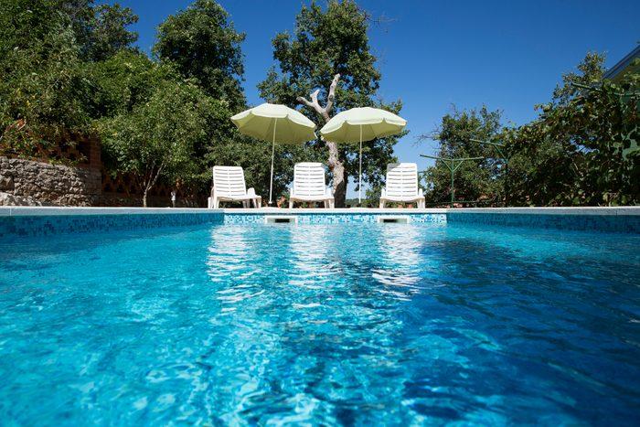 Croatia, Istria, three empty sun loungers at swimming pool