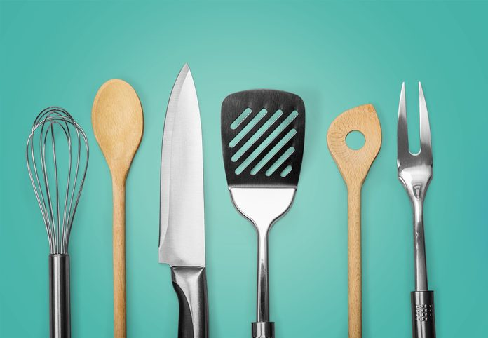 Kitchen metal and wooden utensil on background