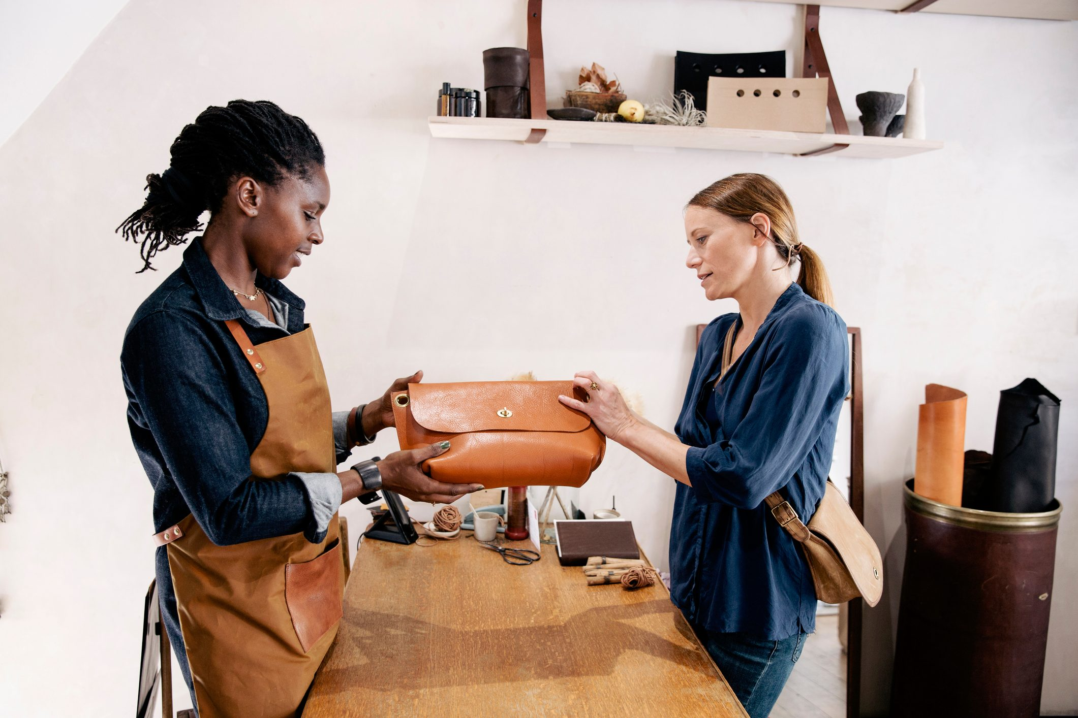 Customer with the owner of a bespoke leather handbag shop