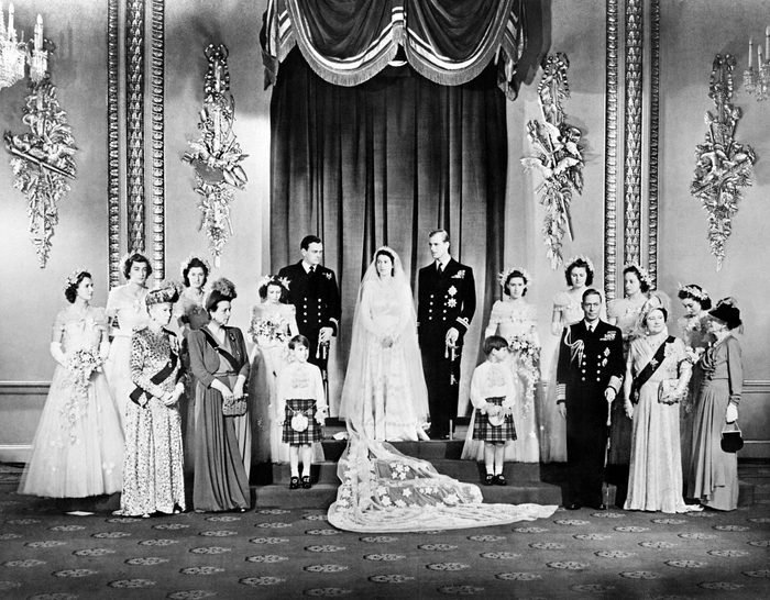Members of the British Royal family and guests pose around Princess Elizabeth (future Queen Elizabeth II) (CL) and Philip, Duke of Edinburgh (CR) (future Prince Philip); at right the group includes Britain's King George VI (5R) stood next to Queen Elizabeth (3R) with Princess Alice of Athlone (R) and in front of bridemaids that include Princess Margaretb (7R) stood next to Philip; at left the group includes the best man David Mountbatten, Marquess of Milford Haven (7L) stood next to Princess Elizabeth, Mary of Teck (3L), mother of King George VI, stands at left in front of the bridesmaids next to Princess Alice of Battenberg (5L), Philip's mother; the page boys are Prince William of Gloucester and Prince Michael of Kent; in the Throne Room at Buckingham Palace on their wedding day November 20, 1947